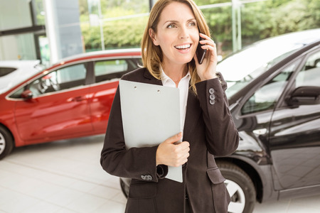 automobile dealership: Smiling saleswoman having a phone call at new car showroom