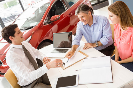 car salesperson: Customers signing some important documents at new car showroom