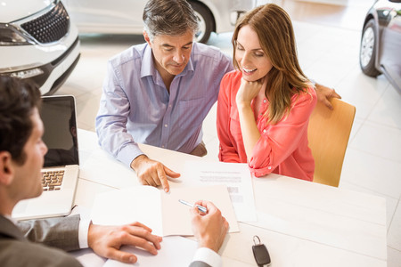 car showroom: Smiling couple buying a new car at new car showroom Stock Photo