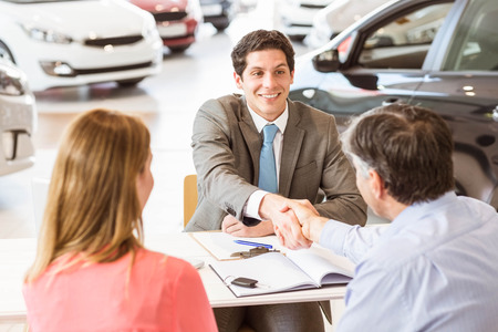 buying: Smiling couple buying a new car at new car showroom Stock Photo
