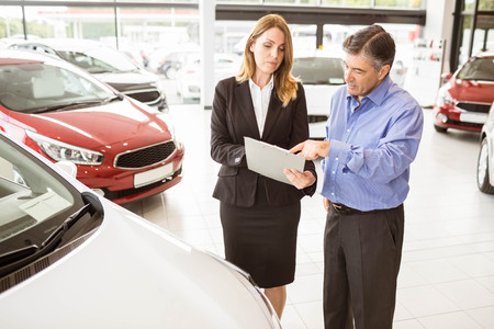 undersign: Focused businessman undersign a car contract at new car showroom