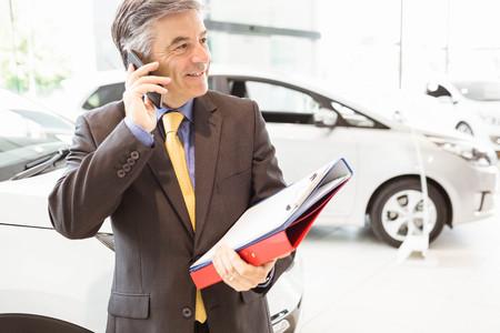 call: Smiling salesman having a phone call at new car showroom