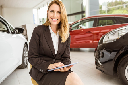car showroom: Smiling saleswoman writing on a clipboard at new car showroom Stock Photo