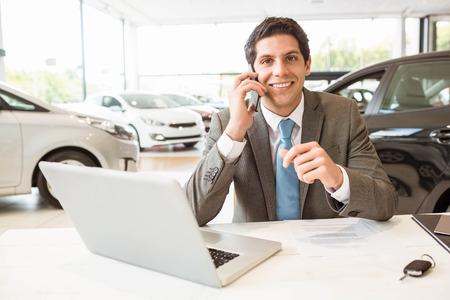 renter: Smiling salesman having a phone call at new car showroom