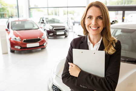 paperwork: Smiling saleswoman holding document while looking at camera at new car showroom