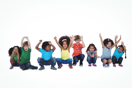 crouching: A row of children crouching down together against a white background