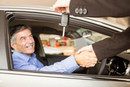 renter: Customer receiving car keys while shaking hand in a garage