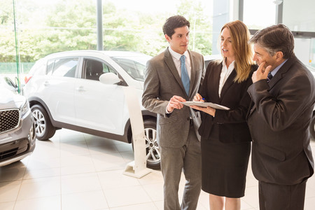 sales team: Sales team look at a clipboard at new car showroom
