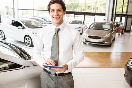 Smiling salesman using tablet near a car at new car showroom Stock Photo