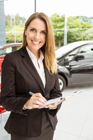 car showroom: Smiling saleswoman checking a car at new car showroom Stock Photo