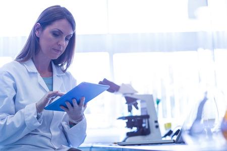 investigador cientifico: Cient�fico que trabaja con una tableta en el laboratorio de la universidad