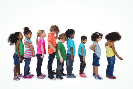 standing in line: Group of kids standing in a line against a white background Stock Photo
