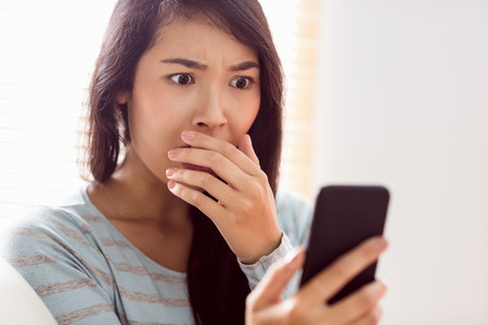 shocked: Asian woman reading shocking text at home in the living room