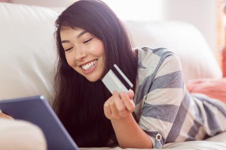Lächelnde asiatische Frau auf Couch mit Tablet, um online zu Hause einkaufen im Wohnzimmer Standard-Bild
