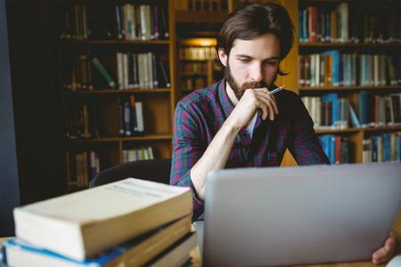 estudiando: Estudiante inconformista que estudia en biblioteca en la universidad