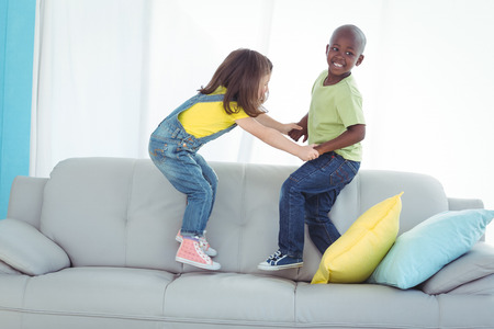 boy room: Happy boy and girl standing up on the couch