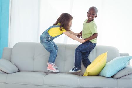 boy jumping: ni�o feliz y una ni�a de pie en el sof�