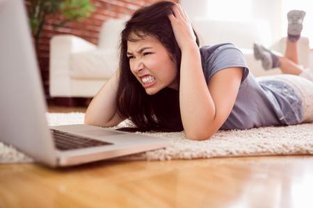 Asian wütende Frau auf dem Boden mit Laptop zu Hause im Wohnzimmer