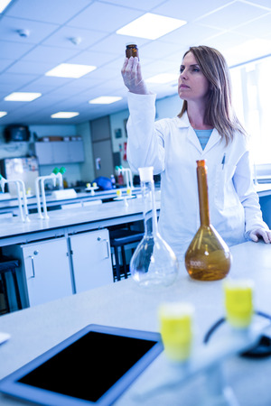biochemist: Scientist looking at beaker of chemical at the university Stock Photo
