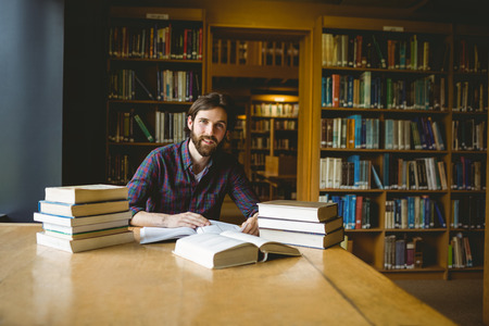 man studying: Hipster student studying in library at the university
