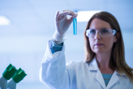 probeta: Científico que mira el tubo de ensayo en el laboratorio en la universidad