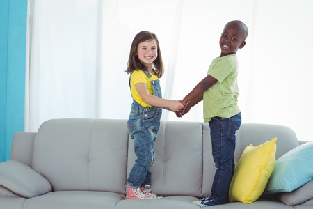 kanapa: Happy boy and girl standing up on the couch