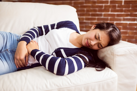 cramps: Asian woman lying on the couch with cramps at home in the living room