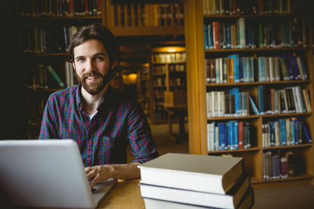 adult student: Hipster student studying in library at the university