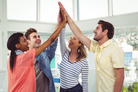 camaraderie: Happy creative team giving a motivational gesture in casual office Stock Photo