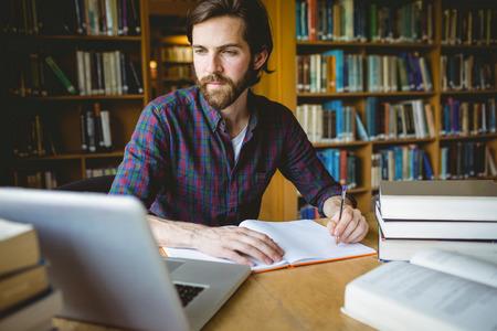 Hipster student studuje v knihovně na univerzitě Reklamní fotografie