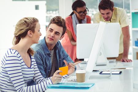 trabajando duro: Equipo de negocios creativos que trabajan duro juntos en el PC en la oficina informal