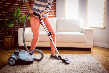 tidying up: Woman hoovering the rug at home in the living room Stock Photo