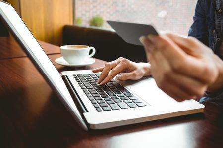Étudiants utilisant un ordinateur portable dans le café de magasiner en ligne à l'université Banque d'images