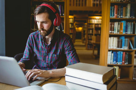 student: Hipster student studying in library at the university