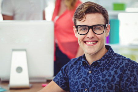 co workers: Smiling creative businessman working near co workers in casual office