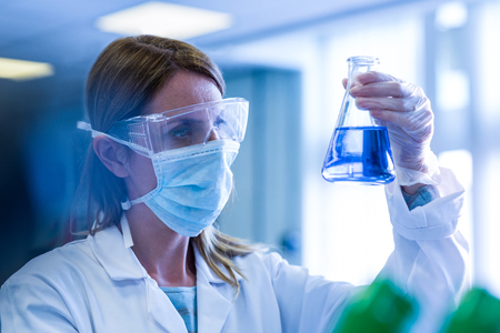 scientist: Scientist holding up beaker of chemical at the university