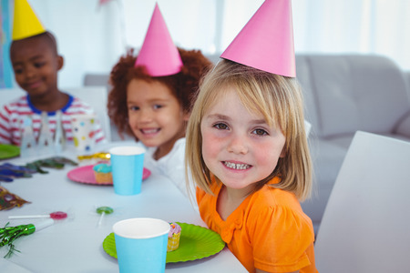 birthday decoration: Excited kids enjoying a birthday party wearing birthday hats