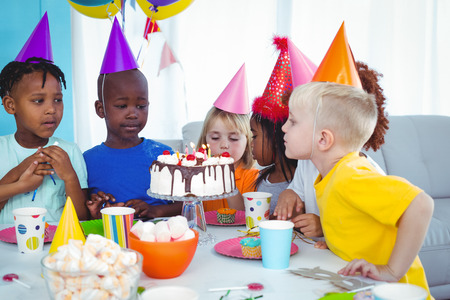 happy birthday girl: Excited kid enjoying a birthday party blowing out the candles Stock Photo