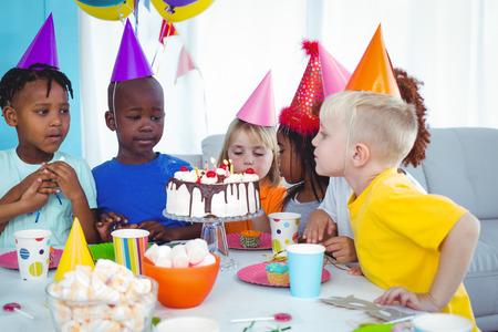 Niño emocionado que disfruta de una fiesta de cumpleaños soplando las velas
