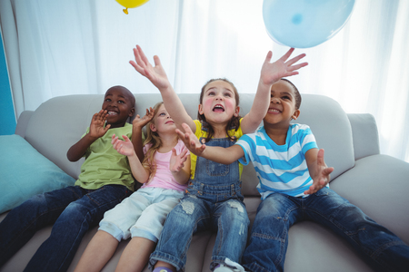kanapa: Smiling kids playing with balloons on the couch Zdjęcie Seryjne