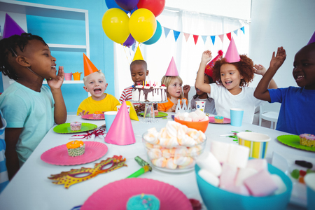 Aufgeregte Kinder genießen eine Geburtstagsfeier mit vielen Süßigkeiten Standard-Bild