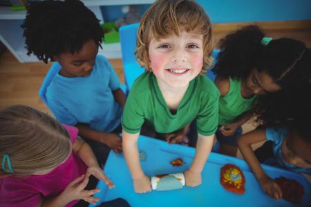 niños negros: Sonriente niños jugando con plastilina en su escritorio