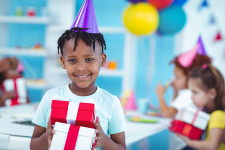 party hat: Happy kids at a birthday party about to open presents