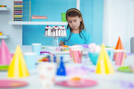Trauriges Kind allein zu ihrer Geburtstagsparty Lizenzfreie Bilder