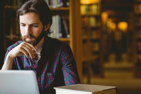 Hipster student studeren in de bibliotheek aan de universiteit