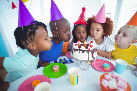 Excited kid enjoying a birthday party blowing out the candles Archivio Fotografico