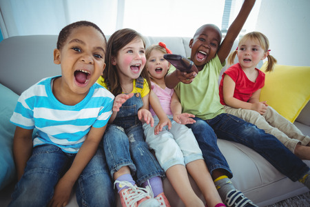 kanapa: Happy kids laughing while sitting down on the couch