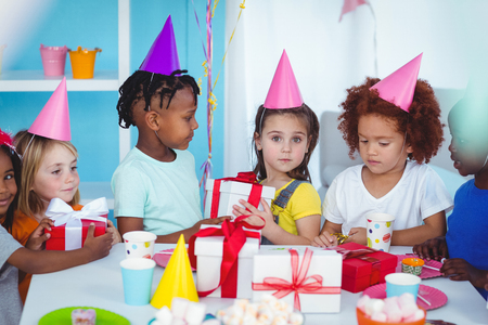 party decoration: Happy kids at a birthday party about to open presents