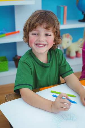 Young boy drawing on paper at their desk
