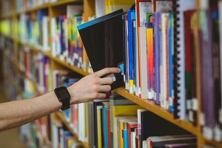 biblioteca: Estudiante que lleva un reloj inteligente en la biblioteca de la universidad